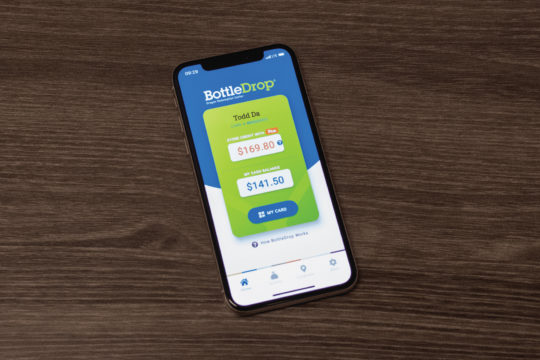 Photo of an iPhone with the BottleDrop app's home screen showing on the phone.