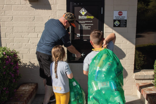 One adult and two kids putting Green Bags into a BottleDrop Redemption Center drop door