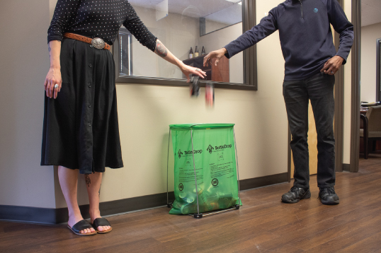Two people putting empty sodas cans in a BottleDrop Green Bag