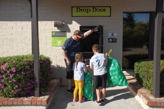 An adult holding open a BottleDrop Redemption Center drop door for two kids to deposit Green Bags