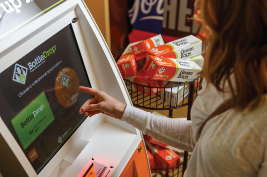 Person using BottleDrop kiosk to get store credit using BottleDrop Plus.