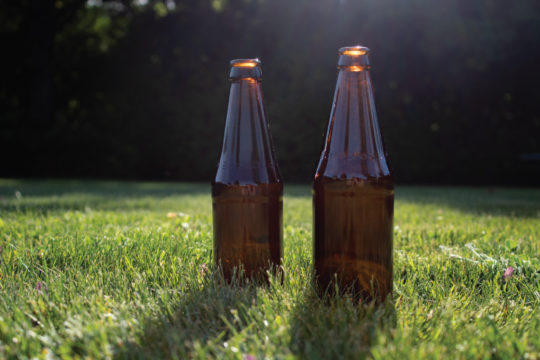 Two refillable glass bottles standing on a lawn.