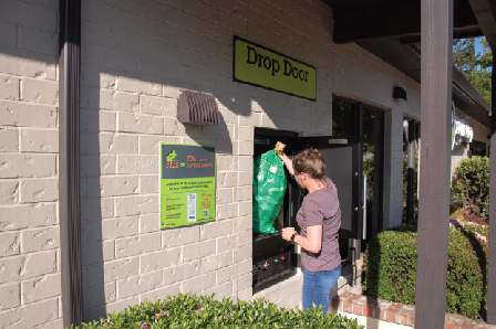 Person dropping off a Green Bag in a BottleDrop Redemption Center drop door