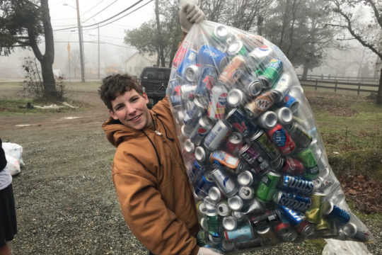 Person holding large bag of empty beverage cans.