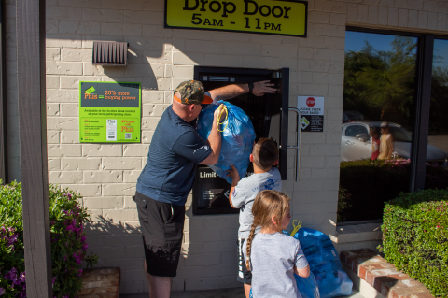 Man and Two Kids Depositing Blue Bags