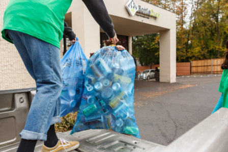 A person standing in a truck bed handing two full BottleDrop Give Blue Bags to a teammate who is going to drop off the bags at the Redemption Center drop door.