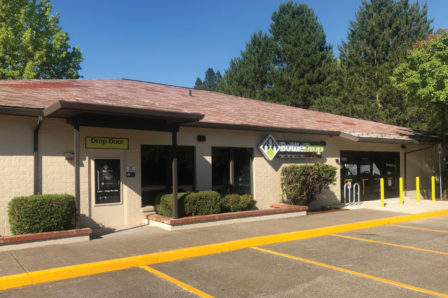 Photo of the exterior of the Corvallis Redemption Center on a bright, spring afternoon.