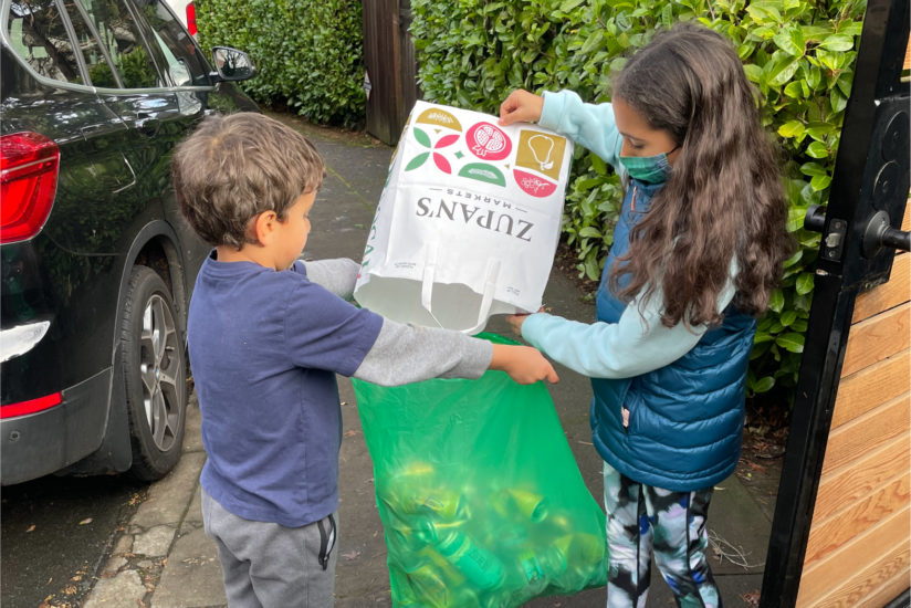 On a sunny day, 5 year old and 9 year old siblings are working together to collect bottles and cans and pour them from a grocery bag into a BottleDrop Green Bag.