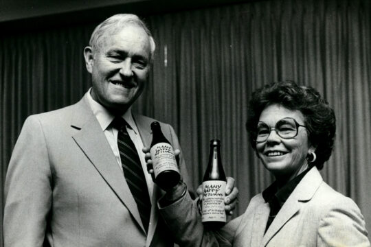 Black and white photo of Oregon Governor Tom McCall and Mary Roberts celebrating the state bottle bill's tenth anniversary.