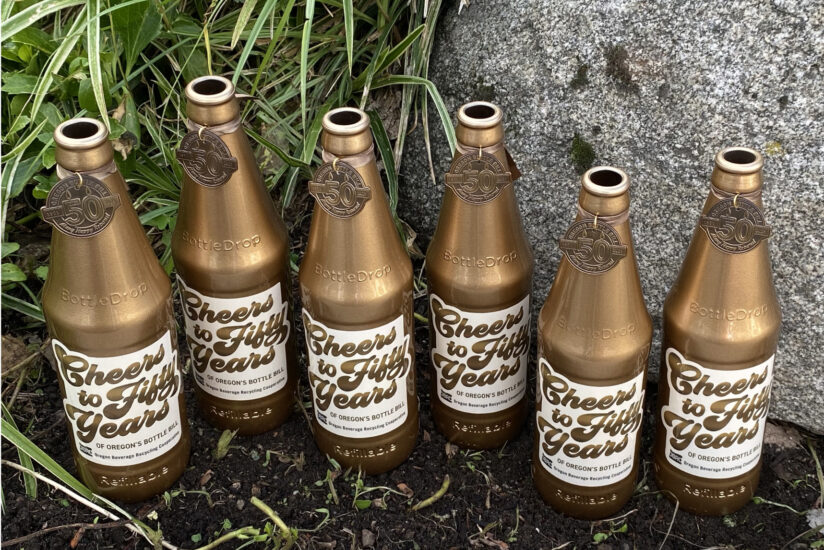 Six golden, commemorative BottleDrop Refillable bottles with a label that says cheers to 50 years of Oregon's bottle bill.