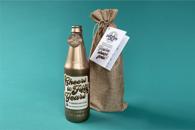 Golden BottleDrop Refillable bottle standing next to a burlap bag with a teal background This one of the six bottles that will be hidden for our celebratory hidden bottle hunt to celebrate 50 years oft Oregon's bottle bill.