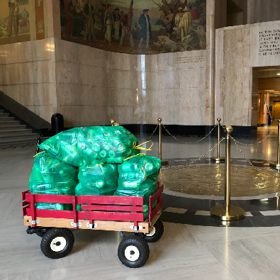 Filled BottleDrop Green Bags in a Radio Flyer wagon sit in the Oregon capitol