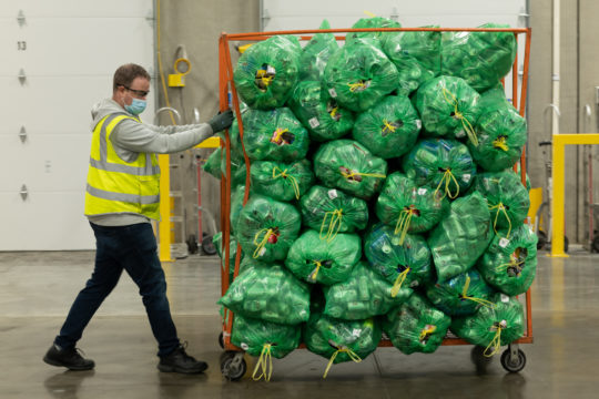 Person pulling a rack of filled BottleDrop Green Bags that are on their way to be processed.