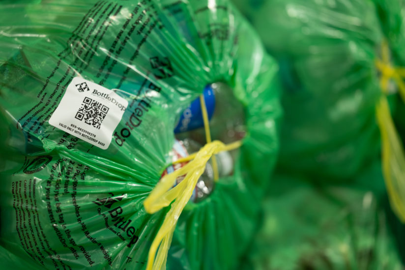 Close up image of a filled BottleDrop Green Bag that is cinched tightly and has a bag tag sticker that identifies it to a specific customer's account.